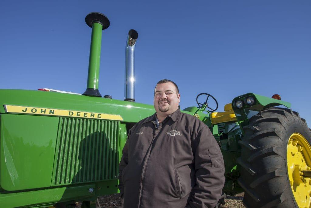 Auctioneer standing by John Deere tractor
